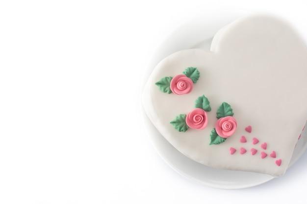 Gâteau coeur pour la saint-valentin, la fête des mères ou un anniversaire, décoré de roses et de coeurs de sucre rose isolé sur fond blanc