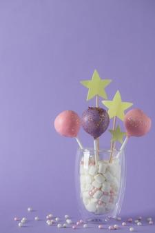 Gâteau coloré apparaît dans un verre avec des guimauves sur un mur violet avec des paillettes. fête, mur d'anniversaire