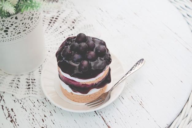 Gâteau court aux bleuets délicieux avec des bleuets frais sur le dessus de table de style vintage.