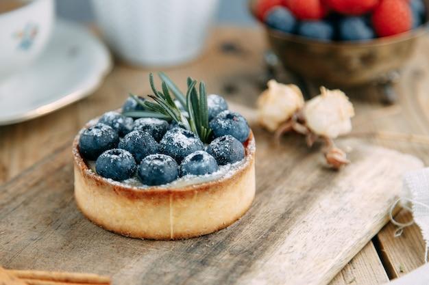 Gâteau à la crème au beurre et aux bleuets sur une assiette. tartelette en gros plan avec des baies et du lait.