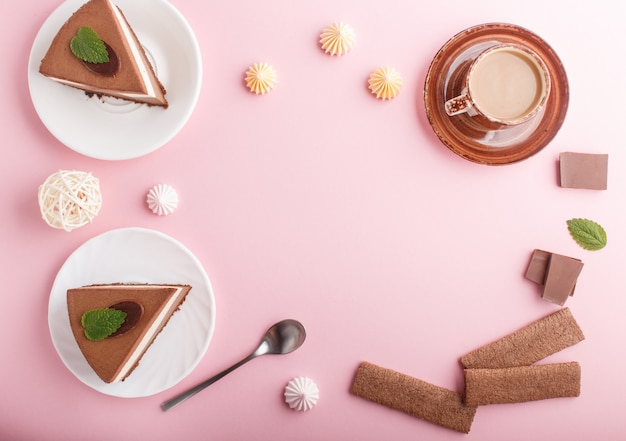 Gâteau à la crème au chocolat au lait souffle avec tasse de meringues au café sur un fond rose pastel