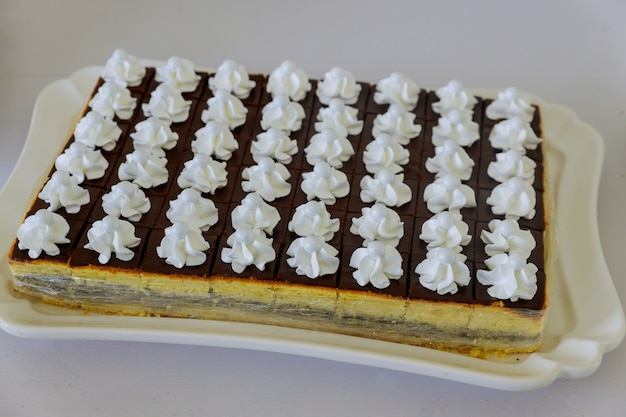 Gâteau à la crème au chocolat rectangulaire décoré de crème au beurre blanche. bonbons de fête.
