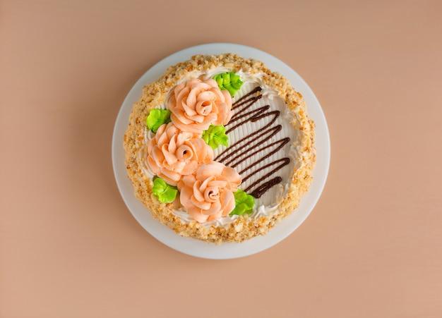 Gâteau à la crème de biscuits avec des roses crémeuses sur la plaque blanche au-dessus de la lumière
