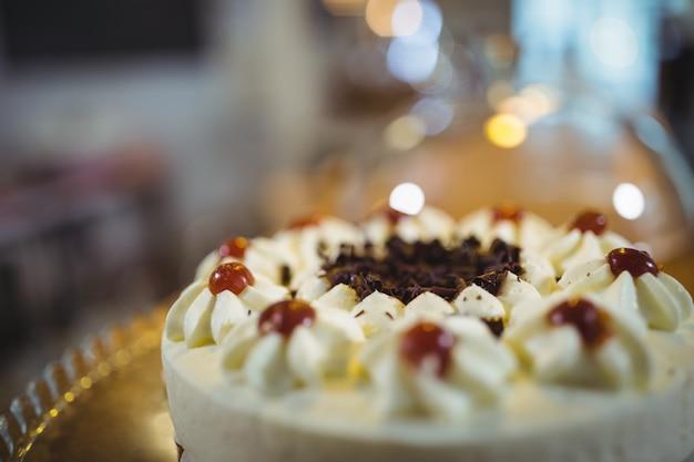 Gâteau à la crème avec la cerise sur la plaque