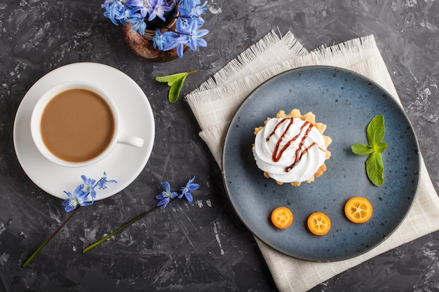 Gâteau à la crème d'œuf fouettée sur une assiette en céramique bleue avec du kumquat et des feuilles de menthe