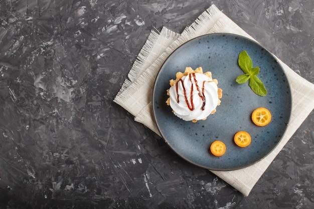Gâteau à la crème d'œuf fouettée sur une assiette en céramique bleue avec des tranches de kumquat et des feuilles de menthe sur un béton noir. vue de dessus, espace copie.