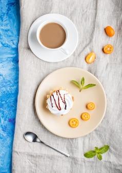 Gâteau à la crème d'œuf fouettée sur une plaque brun clair avec des tranches de kumquat et des feuilles de menthe sur un béton bleu. vue de dessus.
