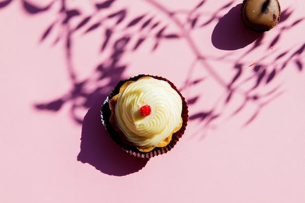 Gâteau à la crème et ombres de branches sur une surface rose. vue ci-dessus