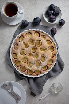 Gâteau crémeux sucré avec des fruits de prunes fraîches dans un plat allant au four blanc avec du sucre en poudre et une tasse de café ou de thé noir sur une surface gris clair