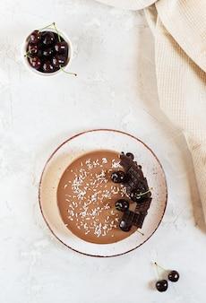 Gâteau cru végétalien au chocolat avec des cerises sur une assiette