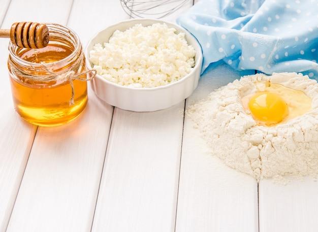 Gâteau de cuisson dans une cuisine rustique - ingrédients de la recette de pâte œufs, farine, lait, beurre, miel sur une table en bois à planches blanches d'en haut. disposition d'arrière-plan avec espace de texte libre.