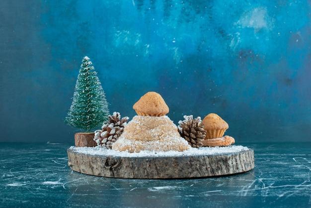 Gâteau, cupcakes, pommes de pin et une figurine d'arbre sur une planche sur bleu.