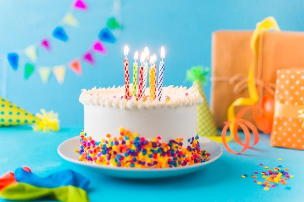 Gâteau décoratif avec une bougie allumée sur fond bleu