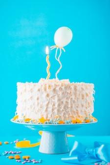 Gâteau décoratif avec une bougie illuminée sur fond bleu