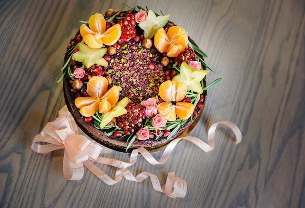 Gâteau décoré de fruits frais, de fleurs et de noisettes.