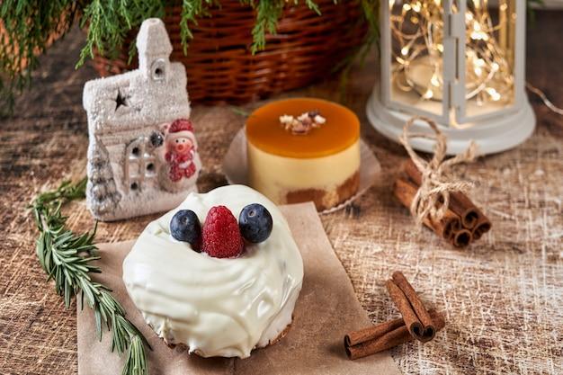 Un gâteau décoré de mûres et de framboises sur une table de noël avec une lampe de poche et une branche d'épinette. nouvel an