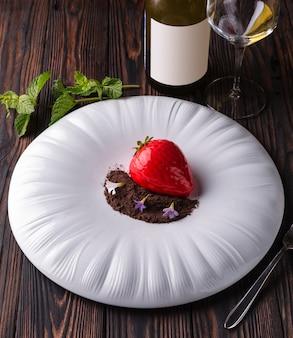 Gâteau dessert aux fraises rouges avec pépites de chocolat et violettes sur une grande assiette blanche.