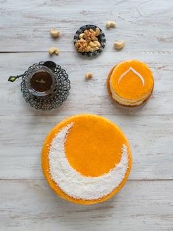 Gâteau doré fait maison avec un croissant de lune, servi avec une tasse de thé et des dattes. mur du ramadan