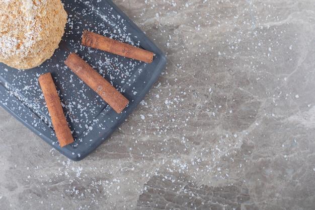 Un gâteau d'écureuil et quelques bâtons de cannelle sur une planche sur une surface en marbre