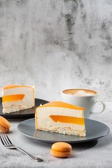Gâteau élégant à la noix de coco, aux fruits de la passion, aux mangues et aux bananes, recouvert de glaçage au chocolat. tranche de gâteau en couches orange sur fond de marbre. fond d'écran pour pâtisserie ou menu de café. verticale.