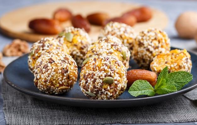 Gateau energy ball avec abricots secs, sésame, lin, noix et dattes sur bleu