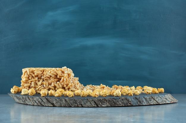 Gâteau enrobé de caramel et un tas de pop-corn au caramel sur une planche sur une surface en marbre