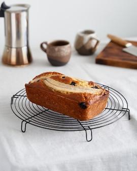 Gâteau entier de pain aux bananes avec banane et myrtilles sur grille, petit-déjeuner du matin avec café