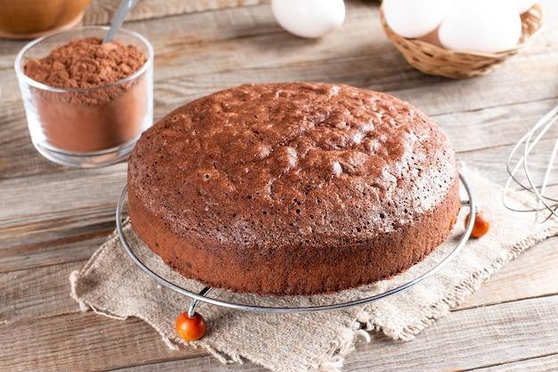 Gâteau éponge au chocolat sur une table en bois avec des ingrédients