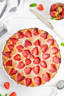 Gâteau éponge aux fraises ou tarte sur un fond en bois blanc avec des fraises fraîches