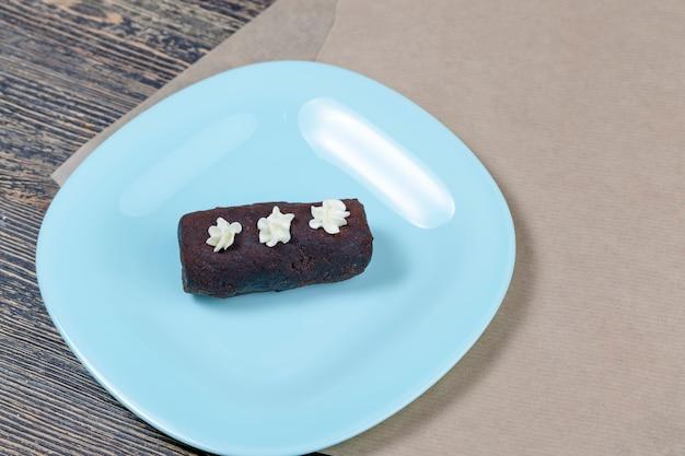 Gâteau éponge à base de pâte et de beurre, garni de poudre de cacao avec des décorations en crème au beurre