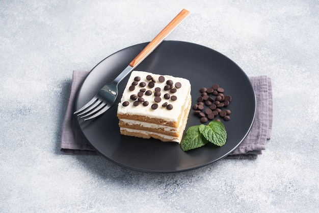 Gâteau éponge avec crème au beurre et morceaux de chocolat à la menthe sur une plaque noire. dessert pour célébrer un événement ou une fête d'anniversaire. vue de dessus, copiez l'espace.