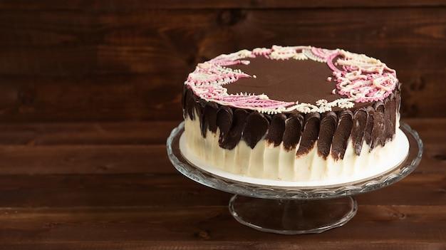 Gâteau éponge avec des motifs mehendi sur le support en verre. fond en bois. mise au point sélective.