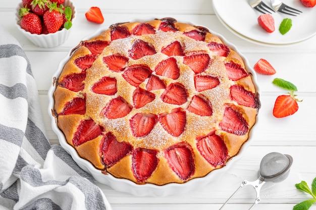 Gâteau éponge ou tarte à la vanille aux fraises sur un fond en bois blanc avec des fraises fraîches