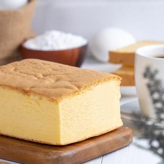 Gâteau éponge traditionnel taïwanais classique ordinaire (castella kasutera taïwanaise) sur une table de fond de plateau en bois avec des ingrédients, gros plan.
