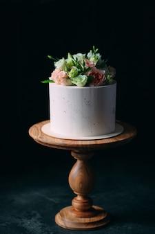 Le gâteau est décoré de fleurs sur un fond sombre.