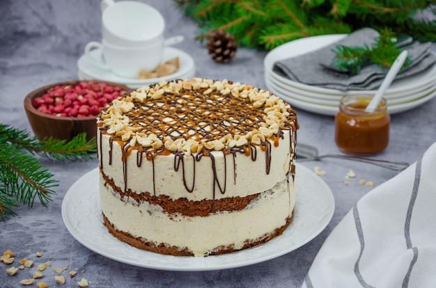 Gâteau étagé festif avec génoise au chocolat, nougat, caramel salé et arachides.