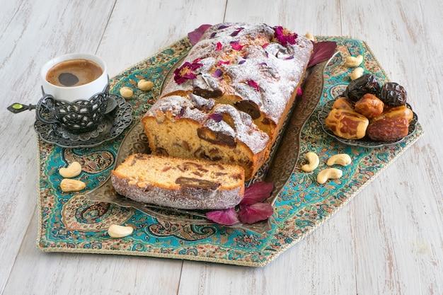 Gâteau fait maison aux dattes et noix, servi avec du café noir sur une table en bois blanc