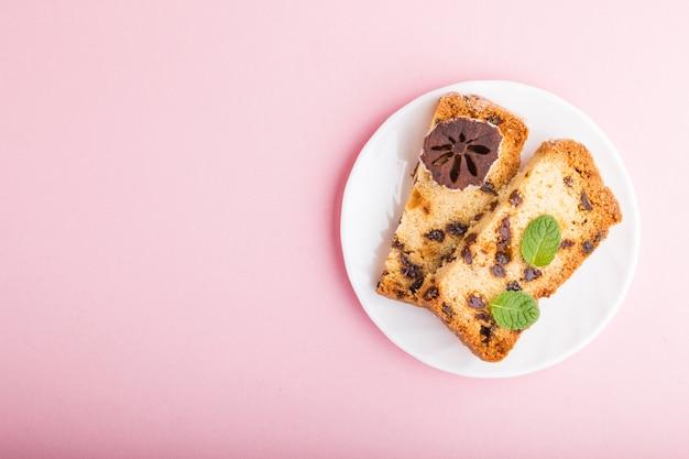 Gâteau fait maison aux raisins secs et kaki séché sur fond rose pastel. vue de dessus, espace copie.