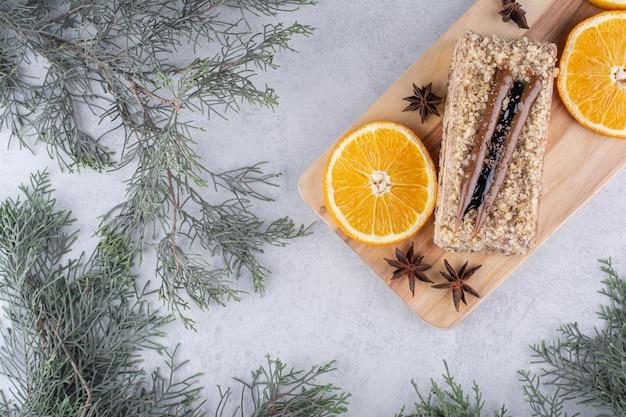 Gâteau fait maison avec des clous de girofle et des tranches d'orange sur planche de bois. photo de haute qualité