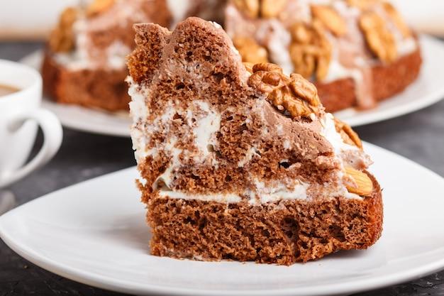 Gâteau fait maison avec crème au lait cacao amande noisette sur un fond de béton noir et une tasse de café