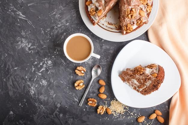Gâteau fait maison avec de la crème de lait, du cacao, des amandes, des noisettes sur du béton noir avec du textile orange et une tasse de café. vue de dessus, espace de copie.