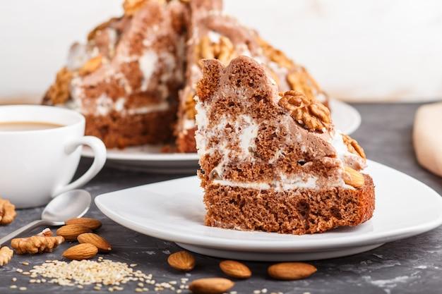 Gâteau fait maison avec de la crème de lait, du cacao, des amandes, des noisettes sur un fond de béton noir et une tasse de café. vue de côté.