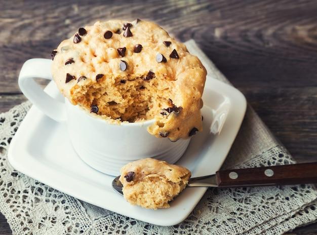 Gâteau fait maison frais dans une tasse avec du beurre d'arachide et des pépites de chocolat sur bois rustique