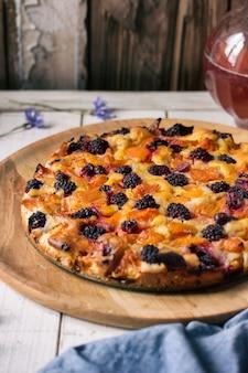 Gâteau fait maison avec mûres, abricots, groseilles à maquereau. le gâteau se dresse sur une table en bois blanche. à côté de la carafe avec une compote rose
