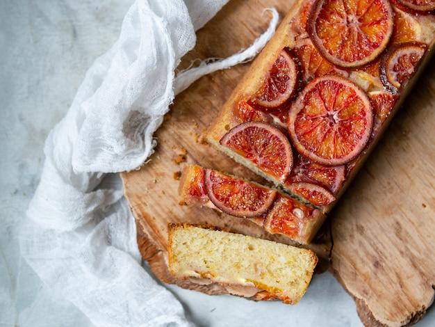 Gâteau fait maison avec des oranges sanguines sur une planche de bois et fond gris clair