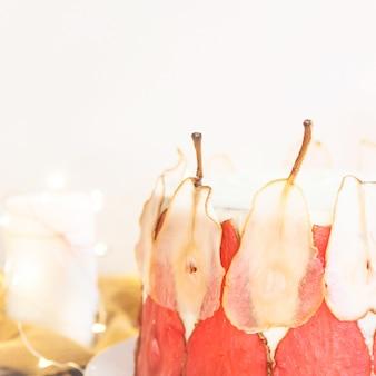 Gâteau de fête blanc décoré de tranches de poires rouges et blanches