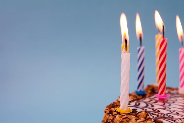 Gâteau de fête avec des bougies sur fond bleu. photo de concept pour les vacances, fête, félicitations. espace copie