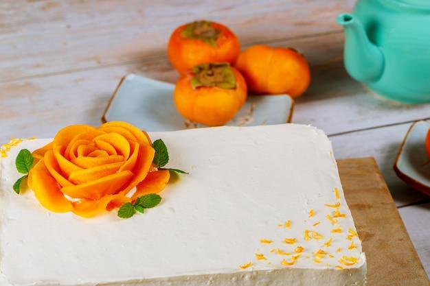 Gâteau de fête à la crème fouettée blanche et tranches de kaki mûr