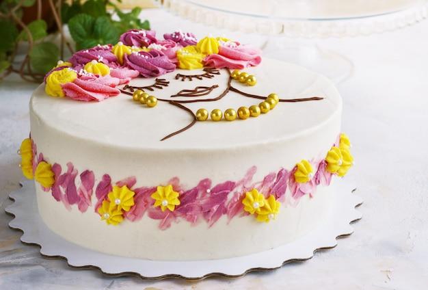 Gâteau de fête avec des fleurs crème et un visage de fille sur fond clair
