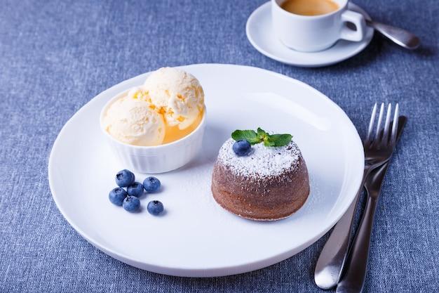 Gâteau fondant au chocolat lava cake avec glace vanille myrtilles menthe et café gros plan